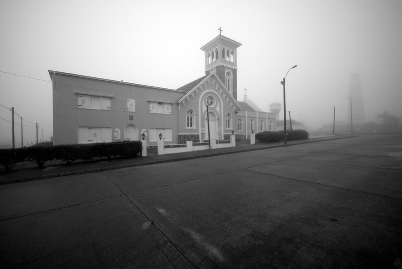 The church called Nuestra Señora de la Candelaria in the fog with the lighthouse of Punta del Este in the background.