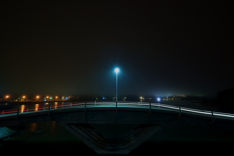 The wavy bridge of La Barra as seen from the side on a foggy night